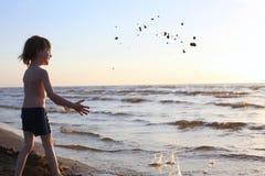 Lyckligt barn som kastar sand till havet Royaltyfria Bilder