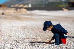 Lyckligt barn som leker med sanden på stranden i sommar Arkivbilder