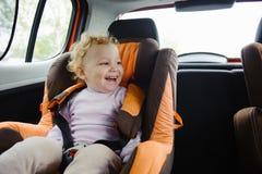 Lyckligt barn som ler i bilsäte arkivbilder