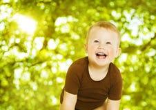 Lyckligt barn som ler över grön bakgrund Slutet behandla som ett barn upp portrai Arkivbild