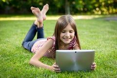 Lyckligt barn som ligger på gräs med den digitala minnestavlan Arkivfoto