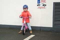 Lyckligt barn som rider en cykel i nedgången Gullig liten flicka i säkerhetshjälm som utomhus rider en cykel Liten flicka på en r Royaltyfria Bilder