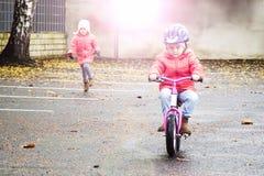 Lyckligt barn som rider en cykel i nedgången Gullig liten flicka i säkerhetshjälm som utomhus rider en cykel Liten flicka på en r Royaltyfri Foto