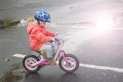 Lyckligt barn som rider en cykel i nedgången Gullig liten flicka i säkerhetshjälm som utomhus rider en cykel Liten flicka på en r Royaltyfri Bild