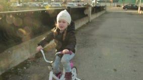 Lyckligt barn som rider en cykel i utomhus- Gullig unge i säkerhetshjälm som utomhus cyklar Liten flicka på en sund röd cykel arkivfilmer