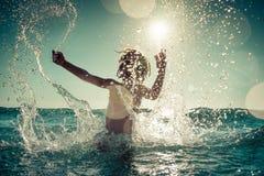 Lyckligt barn som spelar i havet royaltyfri foto