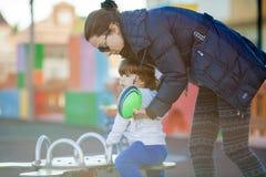 Lyckligt barn som spelar i parkera med deras moder Royaltyfri Foto