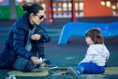 Lyckligt barn som spelar i parkera med deras moder Fotografering för Bildbyråer