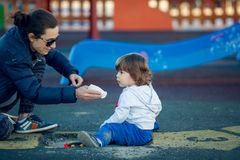 Lyckligt barn som spelar i parkera med hans moder Royaltyfri Bild