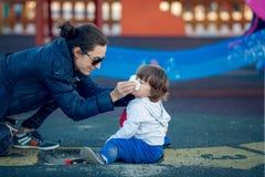 Lyckligt barn som spelar i parkera med hans moder Royaltyfri Fotografi