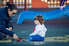 Lyckligt barn som spelar i parkera med hans moder Fotografering för Bildbyråer