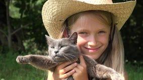 Lyckligt barn som spelar med djur som skrattar flickaståenden med katter utomhus- 4K lager videofilmer