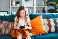 Lyckligt barn som spelar videospel med hemmastadd gamepad royaltyfri fotografi
