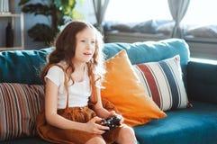 Lyckligt barn som spelar videospel med hemmastadd gamepad arkivbild