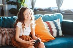 Lyckligt barn som spelar videospel med hemmastadd gamepad royaltyfria foton