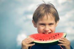 Lyckligt barn som utomhus äter vattenmelon Arkivbilder