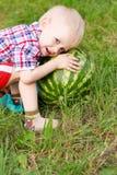 Lyckligt barn som utomhus leker med vattenmelonen Arkivfoton