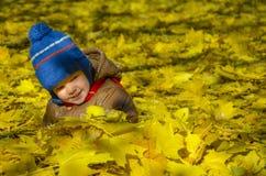 Lyckligt barn utomhus bland de gula sidorna royaltyfri bild