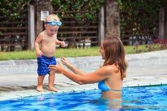 Lyckligt barnbad med den härliga modern i pöl fotografering för bildbyråer