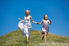 Lyckligt barndombegrepp, moder och dotterinnehavhänder som kör Royaltyfri Fotografi