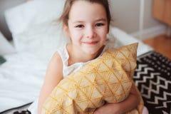 lyckligt barnflickasammanträde på säng och kramar kudde och att vakna upp i otta eller gå att sova Royaltyfria Foton