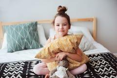 lyckligt barnflickasammanträde på säng och kramar kudde och att vakna upp i otta eller gå att sova Fotografering för Bildbyråer