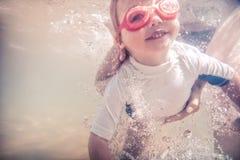 Lyckligt barnlitet barn som lär simning som är undervattens- med instruktören under semester för sommarstrandferier royaltyfria foton