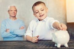 Lyckligt barnsammanträde med hans första moneybox Fotografering för Bildbyråer
