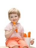 Lyckligt behandla som ett barn äta den nya moroten Royaltyfri Bild