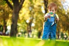 Lyckligt behandla som ett barn att leka med en plånbok i gräsplanen parkerar Arkivfoton