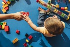 Lyckligt behandla som ett barn att spela med leksakkvarter royaltyfria foton