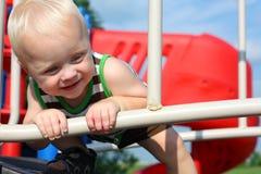 Lyckligt behandla som ett barn att spela på lekplatsen Royaltyfri Fotografi