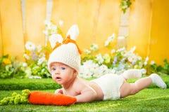 Lyckligt behandla som ett barn barnet kostymerar in en kaninkanin med moroten Arkivfoton