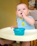 Lyckligt behandla som ett barn den begynnande pojken som äter mål royaltyfri fotografi