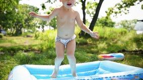 Lyckligt behandla som ett barn flickan som det lilla barnet hoppar på en uppblåsbar luftmadrass - sommar för ultrarapid HD arkivfilmer