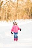 Lyckligt behandla som ett barn flickan i en vinter parkerar Arkivbild