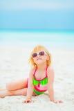 Lyckligt behandla som ett barn flickan i solglasögon som sitter på stranden Arkivfoton