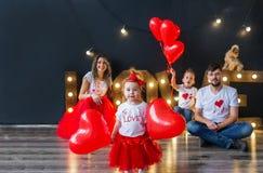 Lyckligt behandla som ett barn flickan med hjärtaballonger och hennes familj som har gyckel på helgonvalentins dag royaltyfria bilder