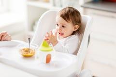 Lyckligt behandla som ett barn flickan med mat och drinken som hemma äter Arkivfoton