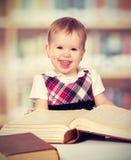 Lyckligt behandla som ett barn flickan som läser en bok i ett arkiv royaltyfri fotografi