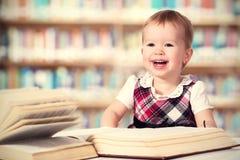 Lyckligt behandla som ett barn flickan som läser en bok i ett arkiv royaltyfri foto