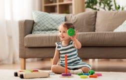 Lyckligt behandla som ett barn flickan som spelar med leksakkvarter hemma arkivbilder