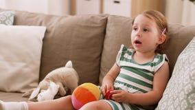 Lyckligt behandla som ett barn flickasammanträde på soffan med hemmastadda leksaker arkivfilmer