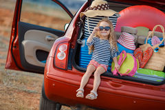 Lyckligt behandla som ett barn flickasammanträde i bilstammen Arkivbild