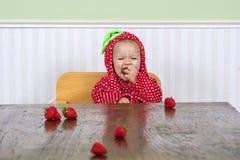 Lyckligt behandla som ett barn i bärdräkten som äter jordgubbar Royaltyfri Foto