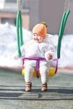 Lyckligt behandla som ett barn i en gunga på en solig vinterdag Royaltyfri Bild