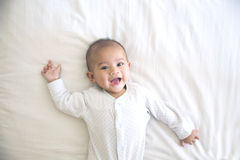 Lyckligt behandla som ett barn le att ligga på en säng Fotografering för Bildbyråer