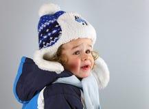 Lyckligt behandla som ett barn lite i en enorm hatt på vitblackground arkivfoto