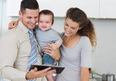 Lyckligt behandla som ett barn med föräldrar som använder den digitala minnestavlan Arkivbild