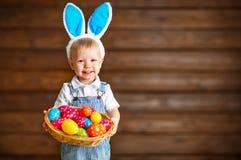 Lyckligt behandla som ett barn pojken i dräkt för påskkanin med korgen av ägg Arkivbilder